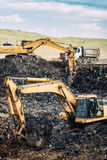 Βαριά βιομηχανικά μηχανήματα, εκσκαφείς που σκάβουν και που φορτώνουν τα φορτηγά εκφορτωτών Στοκ φωτογραφία με δικαίωμα ελεύθερης χρήσης