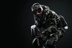 Βαριά οπλισμένος καλυμμένος paintball στρατιώτης που απομονώνεται στο μαύρο υπόβαθρο Έννοια αγγελιών στοκ φωτογραφίες