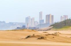 Βαριά φυσώντας άμμος αέρα στην παραλία ενάντια στον ορίζοντα πόλεων Στοκ Φωτογραφίες