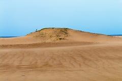 Βαριά φυσώντας άμμος αέρα στην παραλία ενάντια στον παράκτιο ορίζοντα Στοκ Φωτογραφία