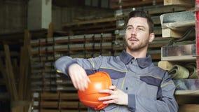 Βαριά χαλάρωση κατασκευαστών βιομηχανίας μετά από το χαμόγελο εργασίας που κοιτάζει μακριά απόθεμα βίντεο