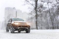 Βαριές χιονοπτώσεις και θολωμένο με κινητήριους τροχούς αυτοκίνητο SUV στο δρόμο 4wd όχημα στην οδό πόλεων στο χειμώνα Εποχιακή έ στοκ εικόνα