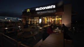 Βαρκελώνη, Ισπανία - 27 Απριλίου 2018: Μια νεολαία συνδέει την κατανάλωση στους θερινούς πίνακες McDonald s αργά το βράδυ McDonal απόθεμα βίντεο
