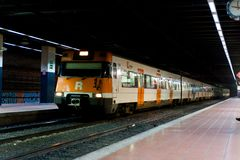 Βαρκελώνη, Ισπανία - 3 Ιανουαρίου 2019: περιφερειακό ισπανικό τραίνο που φθάνει στο μικρό σιδηροδρομικό σταθμό της πόλης με τους  στοκ φωτογραφίες