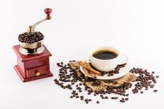 Βαρούλκο μύλων καφέ και φλυτζάνι καφέ με τα φασόλια στο σάκο κάνναβης Στοκ Εικόνα
