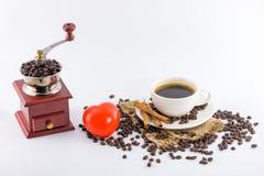 Βαρούλκο μύλων καφέ, κόκκινα εικονίδιο καρδιών και φλυτζάνι καφέ με τα φασόλια στο σάκο κάνναβης Στοκ Εικόνες