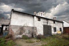 Βαρύθυμη εγκαταλειμμένη αποθήκη εμπορευμάτων με το θυελλώδη ουρανό Στοκ φωτογραφίες με δικαίωμα ελεύθερης χρήσης