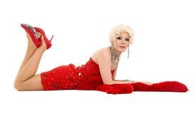Βασίλισσα έλξης στο κόκκινο φόρεμα με τη γούνα που βρίσκεται στο πάτωμα Στοκ φωτογραφίες με δικαίωμα ελεύθερης χρήσης
