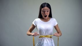 Βασανισμένη γυναίκα που σφίγγει μετρώντας την ταινία στην επιθυμία μέσης της να είναι λεπτός, βουλιμία στοκ εικόνα