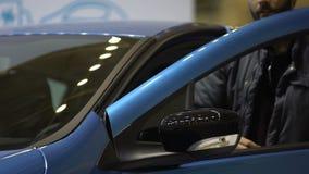Βασική στάση αυτοκινήτων εκμετάλλευσης νεαρών άνδρων κοντά στο νέο λαμπρό αυτοκίνητο, το μίσθωμα και την αγορά φιλμ μικρού μήκους