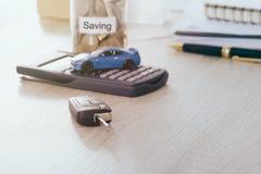 Βασικός μακρινός αυτοκινήτων στο γραφείο με το θολωμένο παιχνίδι αυτοκινήτων στην αποταμίευση υπολογιστών και χρημάτων στην τράπε Στοκ Φωτογραφίες