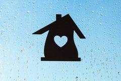 βασικό γλυκό Εγχώριο σύμβολο με μια μορφή καρδιών σε ένα υπόβαθρο παραθύρων με τις ηλιόλουστες πτώσεις της βροχής Στοκ εικόνα με δικαίωμα ελεύθερης χρήσης