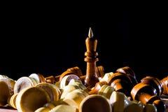 Βασιλιάς σκακιού μεταξύ των πεσμένων κομματιών σκακιού Στοκ Φωτογραφίες