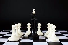 Βασιλιάς σκακιού που περιβάλλεται από τα εχθρικά ενέχυρα Αιχμαλωσία και ήττα Στοκ φωτογραφίες με δικαίωμα ελεύθερης χρήσης