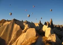 Βασιλικά ballons που πετούν στην ανατολή ανάβουν σε Cappadocia, Τουρκία επάνω από το βράχο formationεδώ κοντά GoremeChimneys στοκ εικόνες