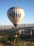 Βασιλικά ballons που πετούν στην ανατολή ανάβουν σε Cappadocia, Τουρκία επάνω από το βράχο formationεδώ κοντά GoremeChimneys στοκ φωτογραφίες