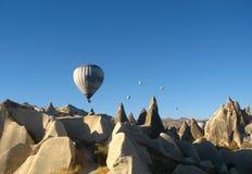 Βασιλικά ballons που πετούν στην ανατολή ανάβουν σε Cappadocia, Τουρκία επάνω από το βράχο formationεδώ κοντά GoremeChimneys στοκ εικόνα με δικαίωμα ελεύθερης χρήσης