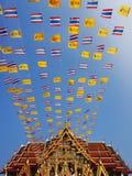 Βασιλικός και εθνικές σημαίες της Ταϊλάνδης που κυματίζει στο μπλε ουρανό Στοκ Εικόνες