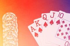 Βασιλικό επίπεδο χέρι καρτών παιχνιδιού στο ζωηρόχρωμο υπόβαθρο με τα τσιπ Στοκ εικόνα με δικαίωμα ελεύθερης χρήσης