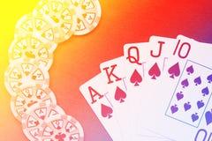 Βασιλικό επίπεδο χέρι καρτών παιχνιδιού στο ζωηρόχρωμο υπόβαθρο με τα τσιπ Στοκ φωτογραφία με δικαίωμα ελεύθερης χρήσης