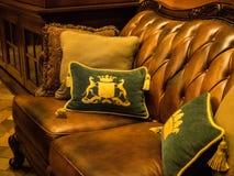 Βασιλικό μοτίβο στα μαξιλάρια με τον καναπέ δέρματος Στοκ Φωτογραφία