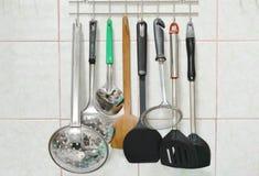 Βατραχοπέδιλο και τρυπητό κουταλών με άλλο σκεύος για την κουζίνα κινητό στην ανοξείδωτη κρεμάστρα στην κουζίνα στοκ φωτογραφίες με δικαίωμα ελεύθερης χρήσης