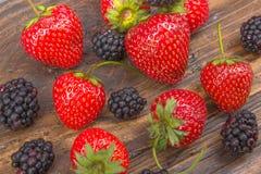 Βατόμουρα, strawberrieson ξύλινο επιτραπέζιο υπόβαθρο, που ανατρέπεται από ένα βάζο καρυκευμάτων Αντιοξειδωτικοοι, detox διατροφή Στοκ Φωτογραφία