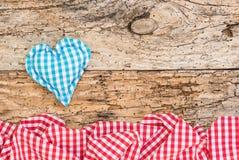Βαυαρικό υπόβαθρο με την μπλε καρδιά και κόκκινα ελεγχμένα σύνορα υφάσματος στο παλαιό ξύλο Στοκ φωτογραφία με δικαίωμα ελεύθερης χρήσης