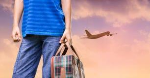 Βαλίτσα και αεροπλάνο εκμετάλλευσης ατόμων που πετούν στον ουρανό ηλιοβασιλέματος Στοκ Εικόνες