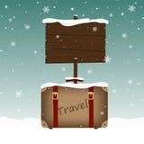 Βαλίτσα ταξιδιού και μια ξύλινη πινακίδα στο χιόνι Στοκ εικόνα με δικαίωμα ελεύθερης χρήσης