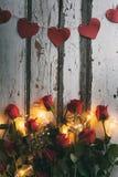Βαλεντίνος: Έμβλημα καρδιών επάνω από τα κόκκινες τριαντάφυλλα και τις λάμπες φωτός Στοκ Εικόνα