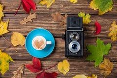 Βγάζει φύλλα, φλυτζάνι καμερών και καφέ στοκ εικόνα