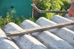 Βγάλτε τα καρφιά από τα παλαιά κεραμίδια στεγών αμιάντων Η επισκευή εργαζομένων στεγών και αφαιρεί τα επικίνδυνα κεραμίδια στεγών Στοκ Εικόνα