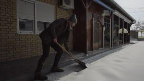 βγαίνοντας σιταποθήκη ατόμων που καθαρίζει φτυαρίζοντας το φρέσκο χιόνι στο ναυπηγείο απόθεμα βίντεο