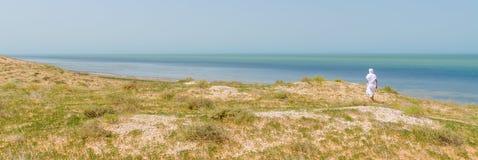 Βεδουίνος στην άσπρη τήβεννο που αγνοεί τον Ατλαντικό Ωκεανό από τους αμμόλοφους Banc στο εθνικό πάρκο δ Arguin, Μαυριτανία, Βόρε στοκ εικόνα