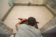Βελτίωση εγχώριων κεραμιδιών - handyman με το επίπεδο που καθορίζει το πάτωμα κεραμιδιών Έννοια ανακαίνισης και κατασκευής στοκ εικόνα