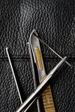 Βελόνα στα χειρουργικά τσιμπιδάκια χειρουργικών νυστεριών κατόχων βελόνων σε ένα μαύρο υπόβαθρο δέρματος στοκ φωτογραφίες