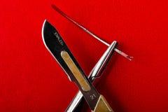 Βελόνα στο χειρουργικό νυστέρι κατόχων βελόνων σε ένα κόκκινο υπόβαθρο στοκ εικόνες