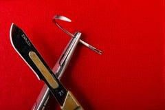 Βελόνα στο χειρουργικό νυστέρι κατόχων βελόνων σε ένα κόκκινο υπόβαθρο στοκ φωτογραφία με δικαίωμα ελεύθερης χρήσης