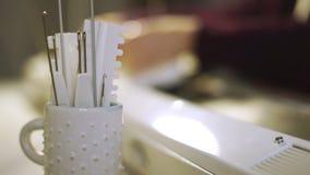 Βελόνες και κυβερνήτες στην άσπρη κούπα για τη χρησιμοποίηση στην πλέκοντας μηχανή στο εργαστήριο απόθεμα βίντεο
