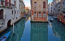 Βενετία, αρχαίο παλάτι στη μέση του καναλιού Μια μικρή βάρκα πλέει στοκ φωτογραφία