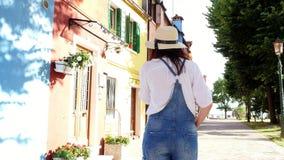 Βενετία, Burano, Ιταλία - 7 Ιουλίου 2018: νέα γυναίκα, κορίτσι στα γυαλιά ήλιων, καπέλο, σορτς, που μιλά στο τηλέφωνο, χαμόγελο απόθεμα βίντεο