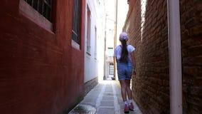 ΒΕΝΕΤΙΑ, ΙΤΑΛΙΑ - 7 ΙΟΥΛΊΟΥ 2018: κατά μήκος μιας στενής οδού της Βενετίας, μεταξύ των παλαιών σπιτιών, ένα κορίτσι εφήβων, ένα π απόθεμα βίντεο