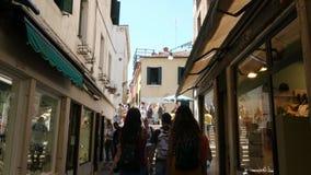 ΒΕΝΕΤΙΑ, ΙΤΑΛΙΑ - 7 ΙΟΥΛΊΟΥ 2018: οδοί αγορών της Βενετίας, πολλά καταστήματα, καταστήματα αναμνηστικών Οι τουρίστες ψωνίζουν για φιλμ μικρού μήκους