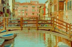 ΒΕΝΕΤΙΑ, ΙΤΑΛΙΑ - 18 ΙΟΥΝΊΟΥ 2015: Εκλεκτική εστίαση της ξύλινης γέφυρας στη Βενετία, pinturesque χρωματισμένη γειτονιά πίσω Στοκ Φωτογραφία