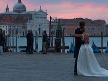 ΒΕΝΕΤΙΑ, ΙΤΑΛΙΑ - 8 ΟΚΤΩΒΡΊΟΥ 2017: νύφη και νεόνυμφος που αγκαλιάζουν στην πλατεία SAN Marco, γόνδολες στο υπόβαθρο Στοκ Εικόνες