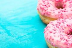 Βερνικωμένα ροζ doughnuts με τη ζάχαρη ψεκάζουν στο ανοικτό μπλε υπόβαθρο, copyspace, γενέθλια, κάρτα, αφίσα, κείμενο έτοιμο Στοκ Εικόνες