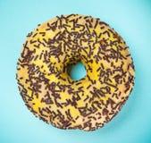 Βερνικωμένο doughnut με ζωηρόχρωμο ψεκάζει στο μπλε υπόβαθρο κρητιδογραφιών Στοκ Φωτογραφία