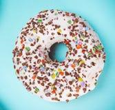 Βερνικωμένο doughnut με ζωηρόχρωμο ψεκάζει στο μπλε υπόβαθρο κρητιδογραφιών Στοκ Φωτογραφίες