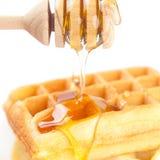 Βελγικές βάφλες σε ένα πιάτο, το ραβδί για το μέλι και το μέλι Στοκ Φωτογραφία